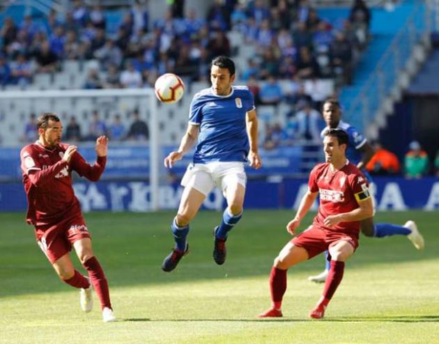 Alfaro busca la segunda jugada tras el control del jugador del Oviedo, como Miguel de las Cuevas