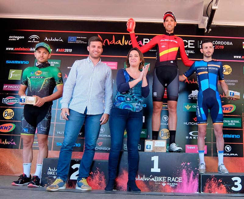 Víctor Manuel Fernández en el tercer escalón del podio final de la Andalucía Bike Race junto al ganador David Valero, con la alcaldesa y Martín Torralbo delante