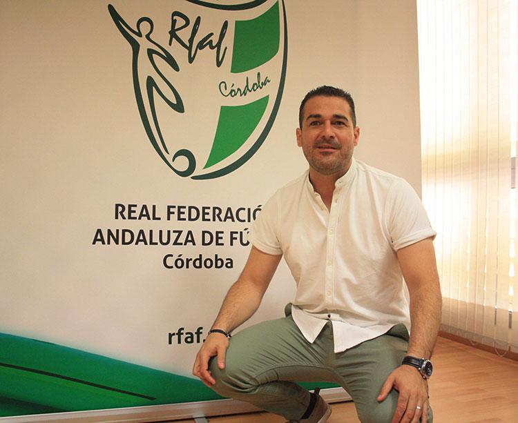 Pablo Lozano posando ante el cartel de la Andaluza en la delegación cordobesa