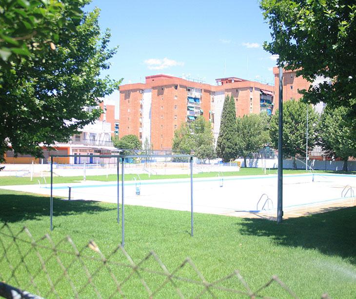 Vista de la piscina de la Fuensanta sin agua y con el césped más que alto
