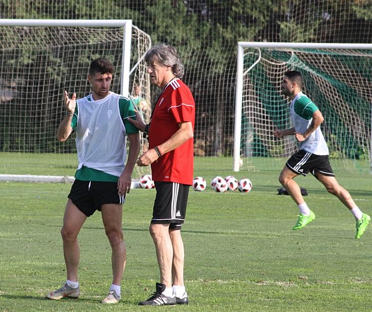 El entrenador blanquiverde, Enrique Martín, hablando con el jugador Javi Flores.