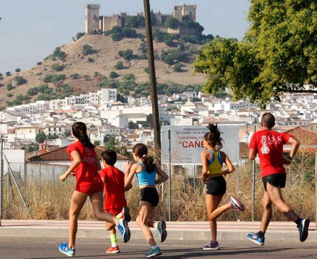 Varios atletas corriendo con el Castillo de Almodóvar Del Río al fondo.