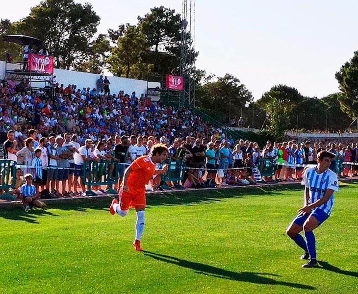 Raúl Cámara centrando ante un jugador del Málaga con la grada de Coín repleta