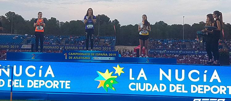 Carmen Romero aplaudiendo a sus compañeras de podio.