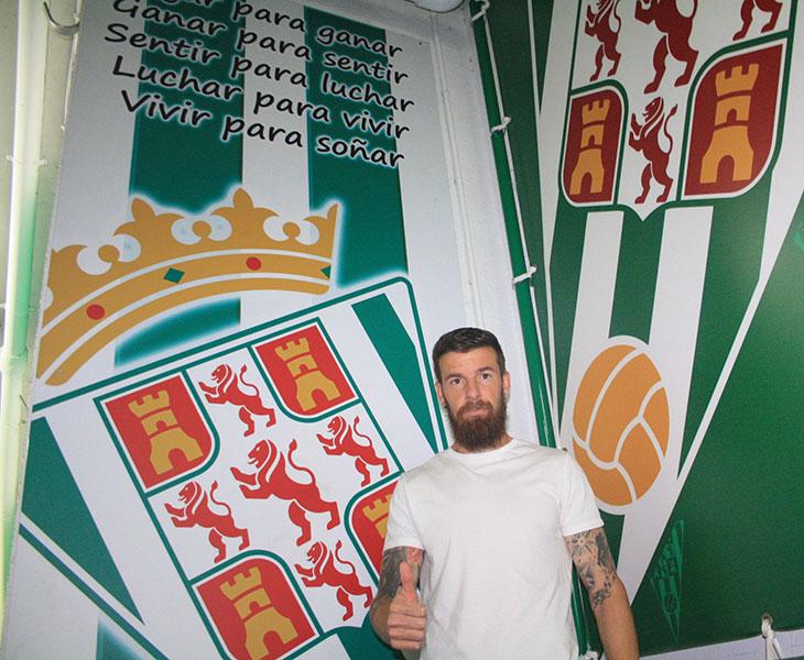 Chus Herrero ante el escudo del Córdoba en la bocana de vestuarios