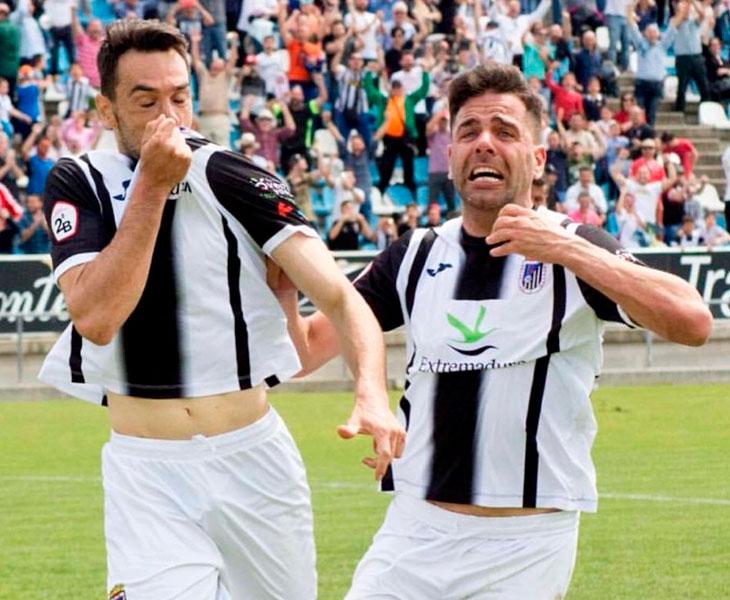 Guzmán besando el escudo del club de su tierra celebrando un gol junto a un compañero