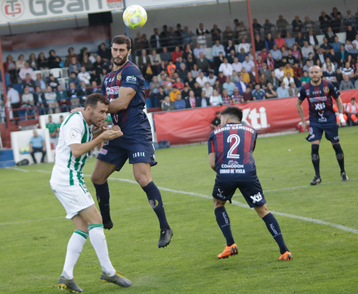 Imanol García llegando tarde a un balón aéreo ante un jugador del Yeclan