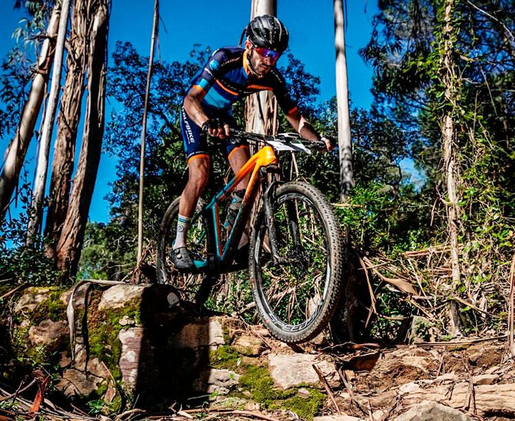 Víctor Manuel Fernández descendiendo con su bicicleta por una zona de arboledas y rocas