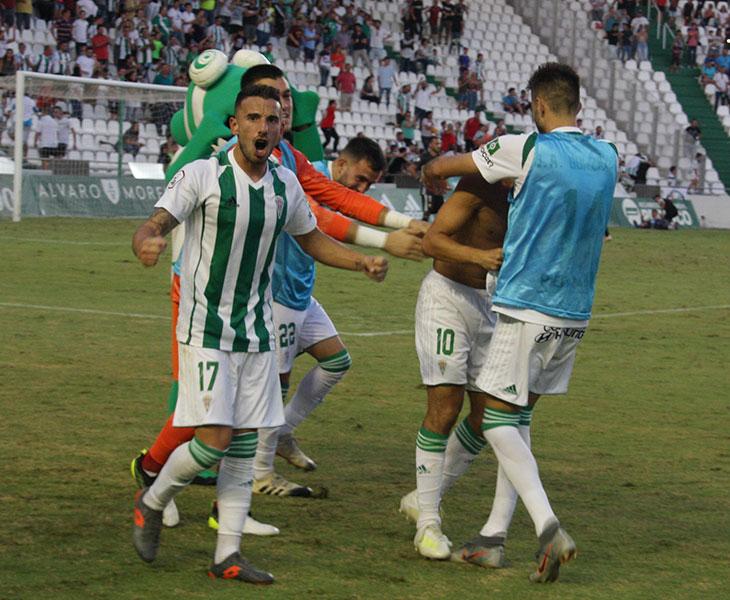 Fernández celebrando el gol con la afición mientras Miguel de las Cuevas se recomponía de la piña que formaron los blanquiverdes