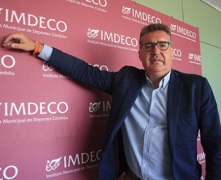 El presidente del IMDECO. Manuel Torrejieno posando junto a una trasera con el logotipo de su concejalía