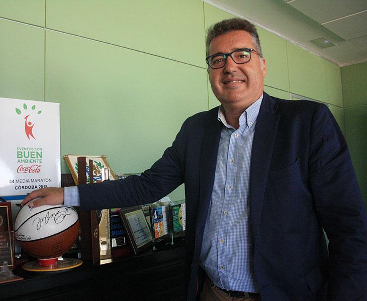 Manuel Torrejimeno posando junto a un balón de baloncesto y otros obsequios de eventos deportivos que pasaron por Córdoba en el pasado