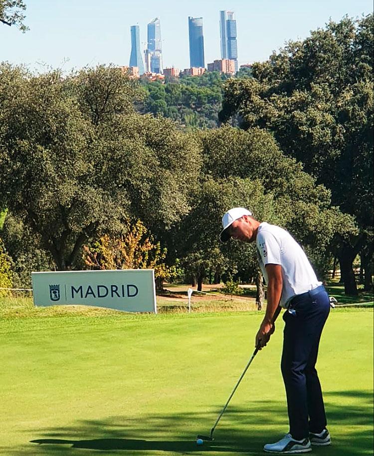 Víctor Pastor en su ronda de prácticas en el Villa de Madrid con los rascacielos de la capital de España al fondo