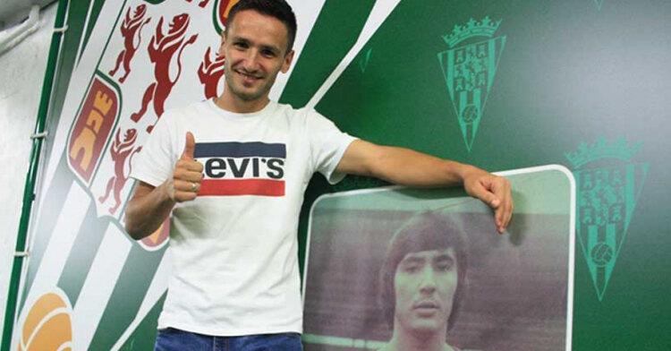 Jovanovic posando junto a la imagen de Rafael Jaén que le recuerda a él cuando vino con su peinado a los Beatles
