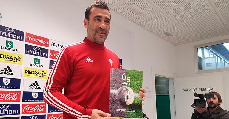 Raúl Agné mostrando la revista de los 65 años de vivencias blanquiverdes de los periodistas deportivos