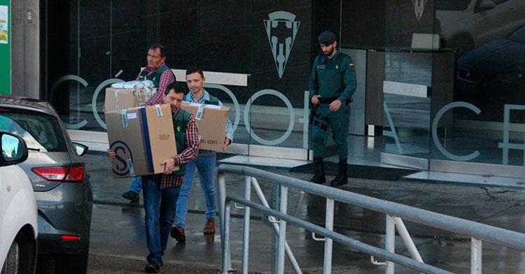 Tres agentes de la policía judicial sacando cajas de El Arcángel con un guardia civil al fondo