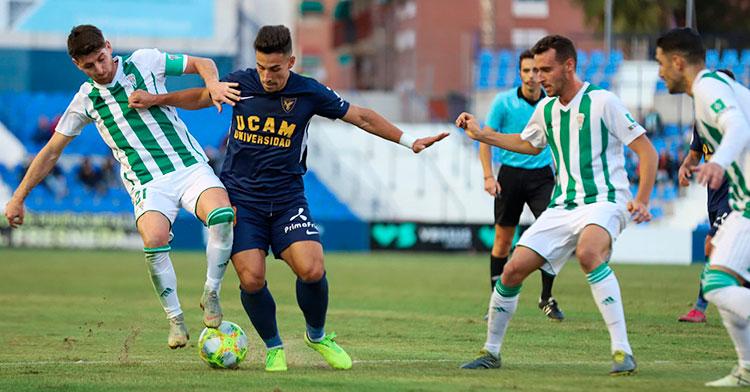 Javi Flores forcejeando con un jugador del UCAM Murcia con Imano García y Víctor Ruiz a la derecha