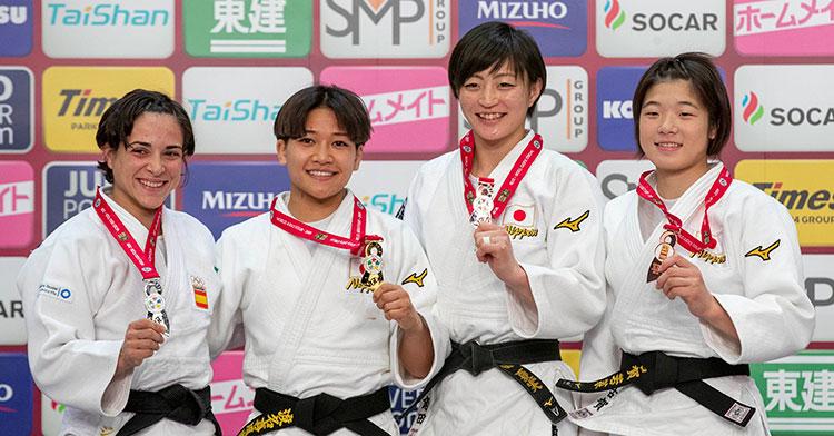 Julia Figueroa, a la izquierda, mostrando su medalla de plata rodeada de japonesas