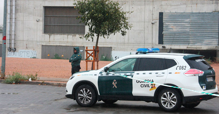 Un guardia civil custodia la zona acotada con una pintada al fondo pidiendo la marcha de Jesús León