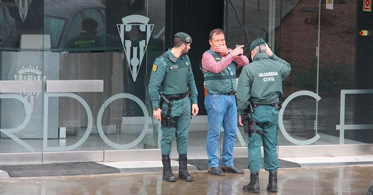 Un policía judicial dando instrucciones a dos guardias civiles en la puerta de acceso a las oficinas de El Arcángel