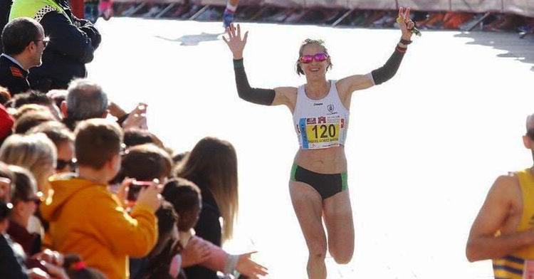 La extremeña Raquel Gómez alza los brazos en señal de triunfo antes de cruzar la meta