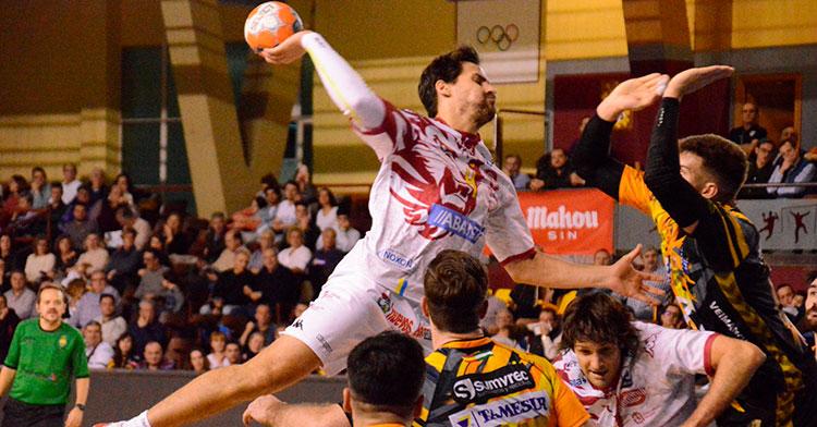 Un jugador del Abanca Ademar de León se levanta sobre la defensa pontana para encara el intento de bloqueo de Ruslan Dashko