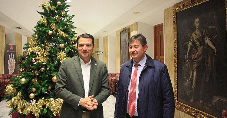 El alcalde José María Bellido posando junto a Javier González con el árbol de Navidad al fondo y San Rafael presente en el cuadro de la derecha