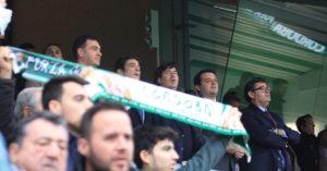 Varios aficionados cantan el himno del Córdoba luciendo la bufanda cordobesita ante el palco de El Arcángel con el alcalde entre los consejeros blanquiverdes.