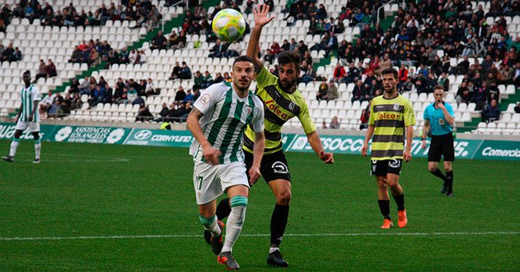 Fernández buscando el balón por delante de dos jugadores del Atlético Sanluqueño
