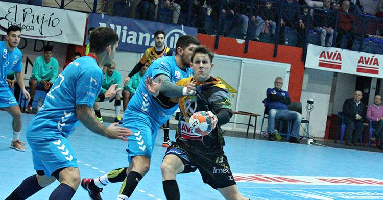 Víctor Alonso intenta penetrar ante dos jugadores del Sinfín