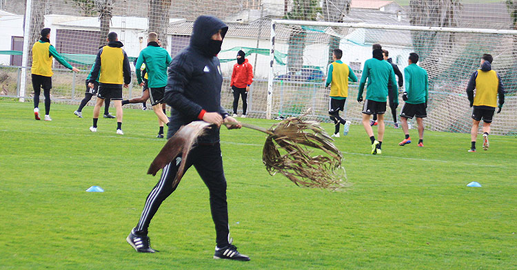 Raúl Agné trasladando una rama de las palmeras que el viento llevó al terreno de juego.