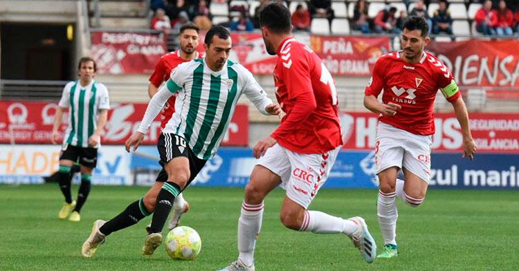 Miguel de las Cuevas en un eslalom entre jugadores del Real Murcia.