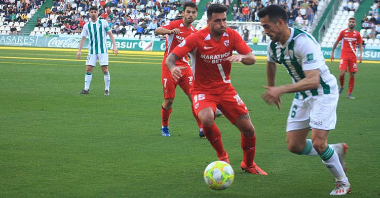 Iván Navarro superando a Álex Robles en su visita a El Arcángel con el Sevilla Atlético a finales de febrero.