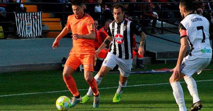 Jesús Álvaro avanzando con el balón ante dos jugadores del CD Badajoz.