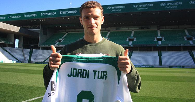 Jordi Tur muestra sus pulgares a la cámara de Cordobadeporte.com sosteniendo la camiseta balanuiverde con su nombre.