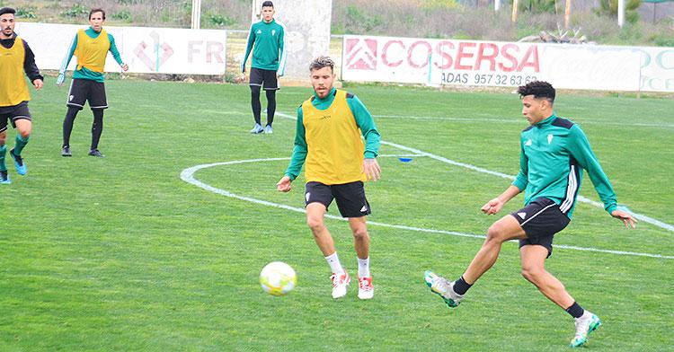 Felipe Veloso pasa el balón ante la llegada de Vera con Raúl Cámara y otros jugadores del primer equipo al fondo.