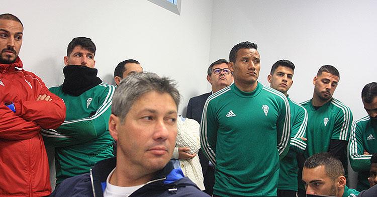 Alfonso Serrano, sentado en los asientos de la sala de prensa, con varios jugadores al fondo y el consejero delegado, Javier González Calvo.