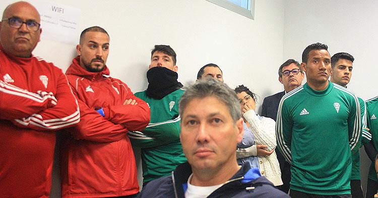 Alfonso Serrano durante la despedida de Raúl Agné con Javier González Calvo al fondo entre los jugadores en la sala de prensa de El Arcángel.