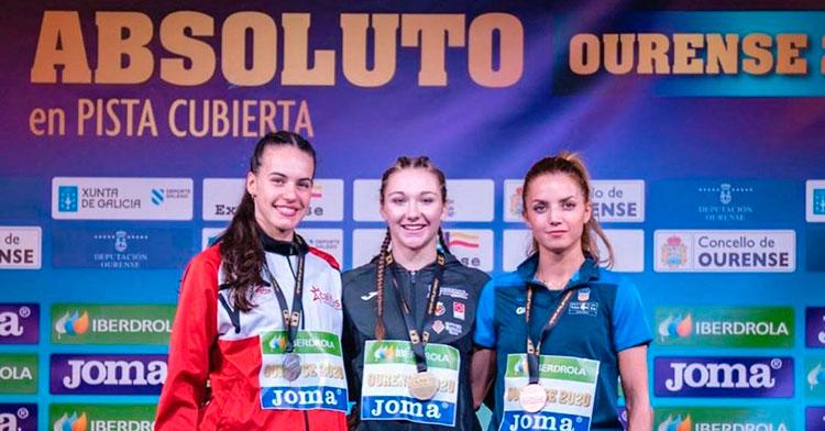 Carmen Avilés, a la izquierda, en el podio del 400 lisos absoluto junto a Andrea Jiménez.
