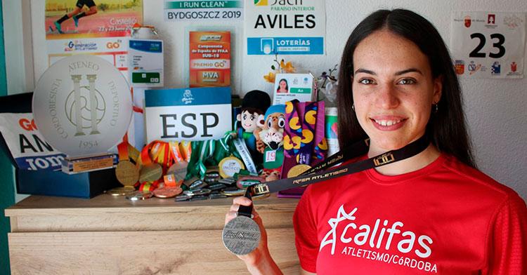Carmen Avilés posando con su presa de plata absoluta y todo su medallero de fondo ya de vuelta en su casa.