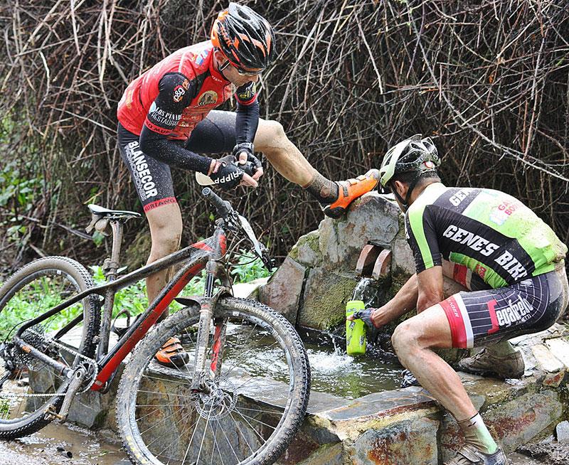 Dos ciclistas de la Guzmán El Bueno refrescándose en mitad del recorrido.