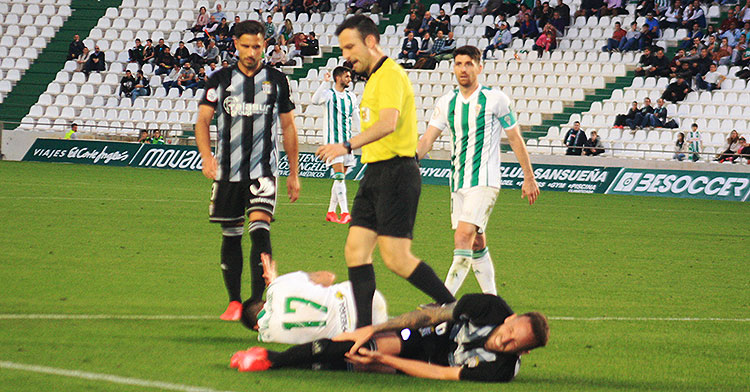 Javi Flores junto a un jugador del Cartagena observan a sus compañeros doloriéndose sobre el césped.