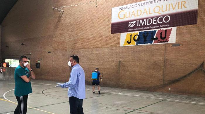 El presidente del IMDECO, Manuel Torrejimeno, departiendo con el gerente de Adecor, Juan Ignacio Gemes, en el pabellón del Guadalquivir mientras un operario hace labores de desinfección en la pista.
