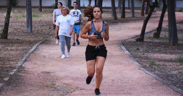 Una runner se emplea a fondo por las pistas de El Tablero con varios corredores andando a su ritmo al fondo.