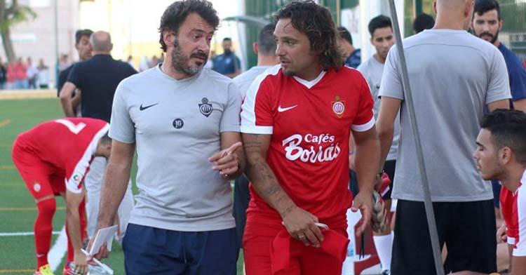 Jesús Galván cambiando impresiones con un jugador del Utrera.