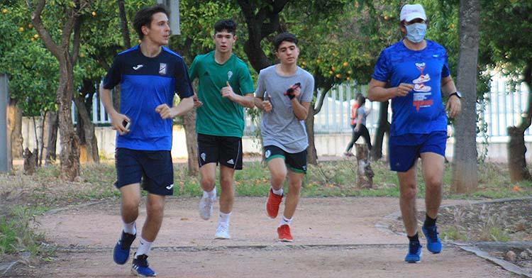 Varios atletas corren por el circuito de El Tablero con un joven integrante de las categorías inferiores del Córdoba CF.