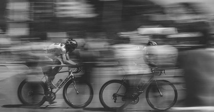 Dos ciclistas pedaleando a gran velocidad en un descenso