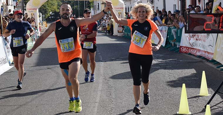 Una pareja de atletas populares cruzando la línea de meta de la Media Maratón de Almodóvar del Río.