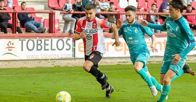 Zelu conduciendo el balón por delante de dos jugadores del filial de Osasuna.