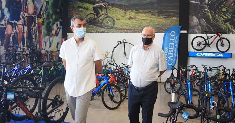 Antonio Cabello junto al director general de la Vuelta a España rodeado de bicicletas.