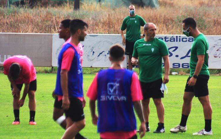 Sabas departiendo con Rubén Bretones ante varios de sus jugadores, con Javi Poveda al fondo.